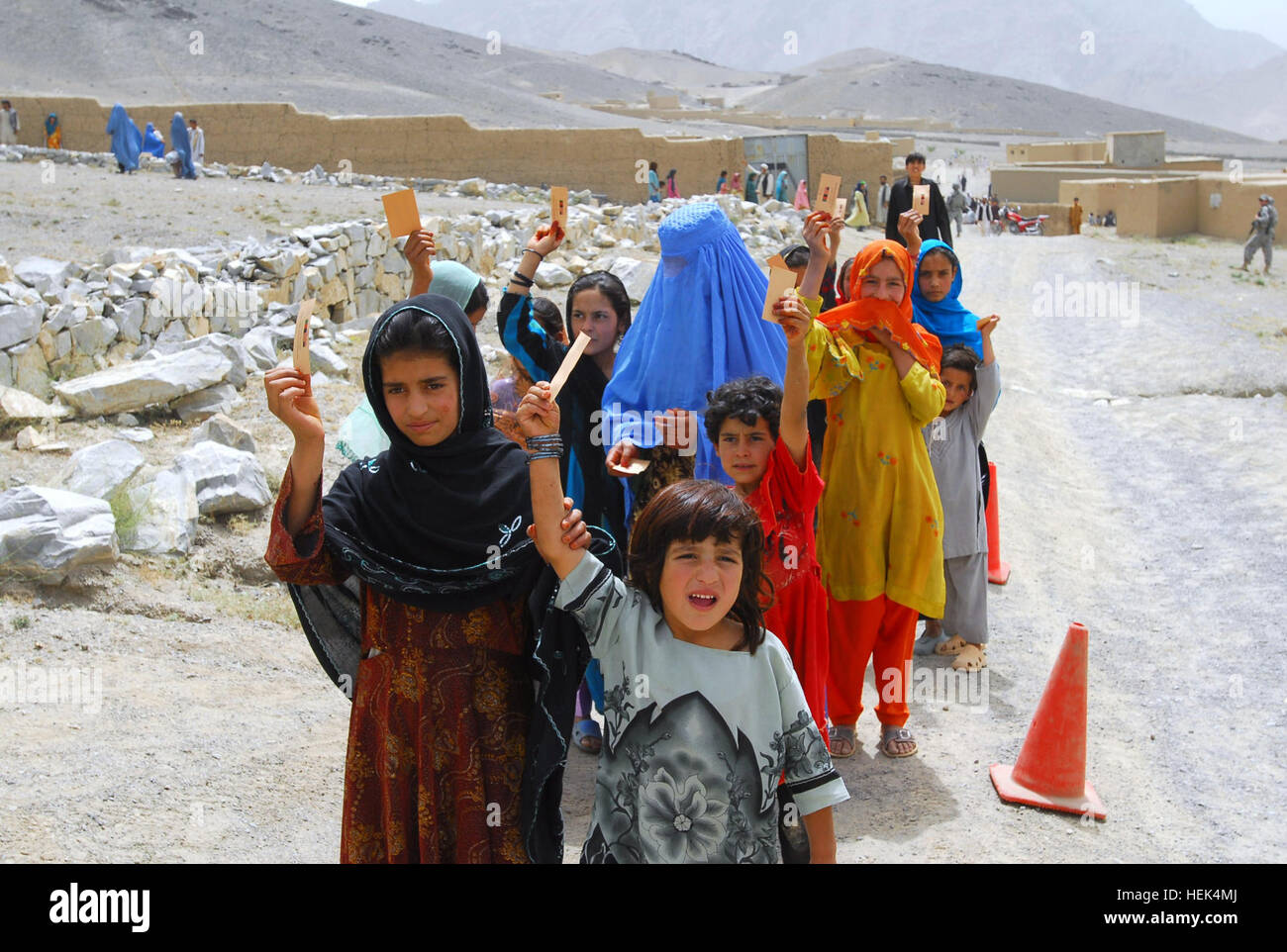 Afghan girls in the Naw Abad Village of Kabul Province hold up their tickets at a humanitarian assistance drop, Stock Photo