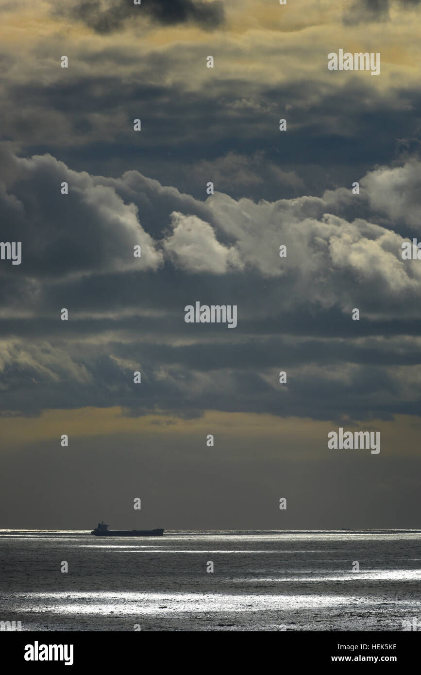 Ship in the distance sailing through the English Channel under a blanket of stormy clouds.  UK, United Kingdom - Stock Image