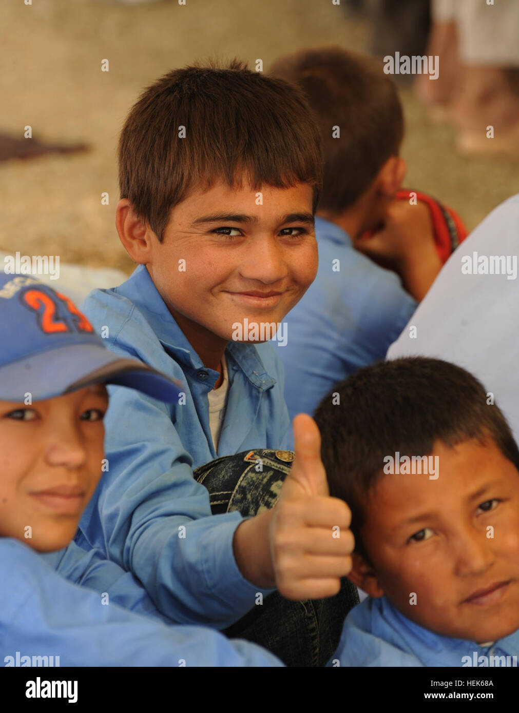 A young Afghan boy shows his approval with a 'thumbs-up' during a ground breaking ceremony at the Aliabad - Stock Image