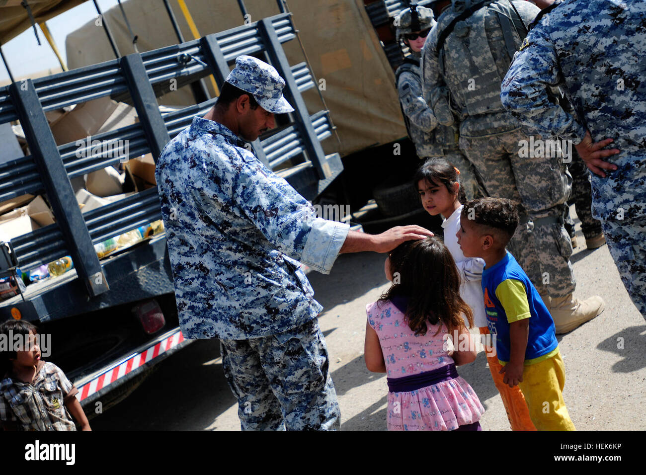 An Iraqi National Police officer speaks with Iraqi children, Oct. 15, during a humanitarian aid mission in eastern - Stock Image
