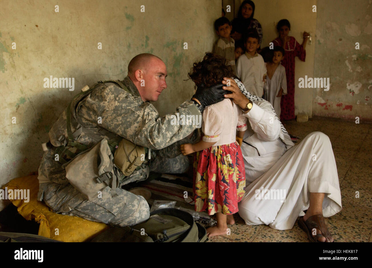 A medic with the 2nd Battalion, 506th Infantry Regiment, treats a young Iraqi girl with burns on her face in Al - Stock Image
