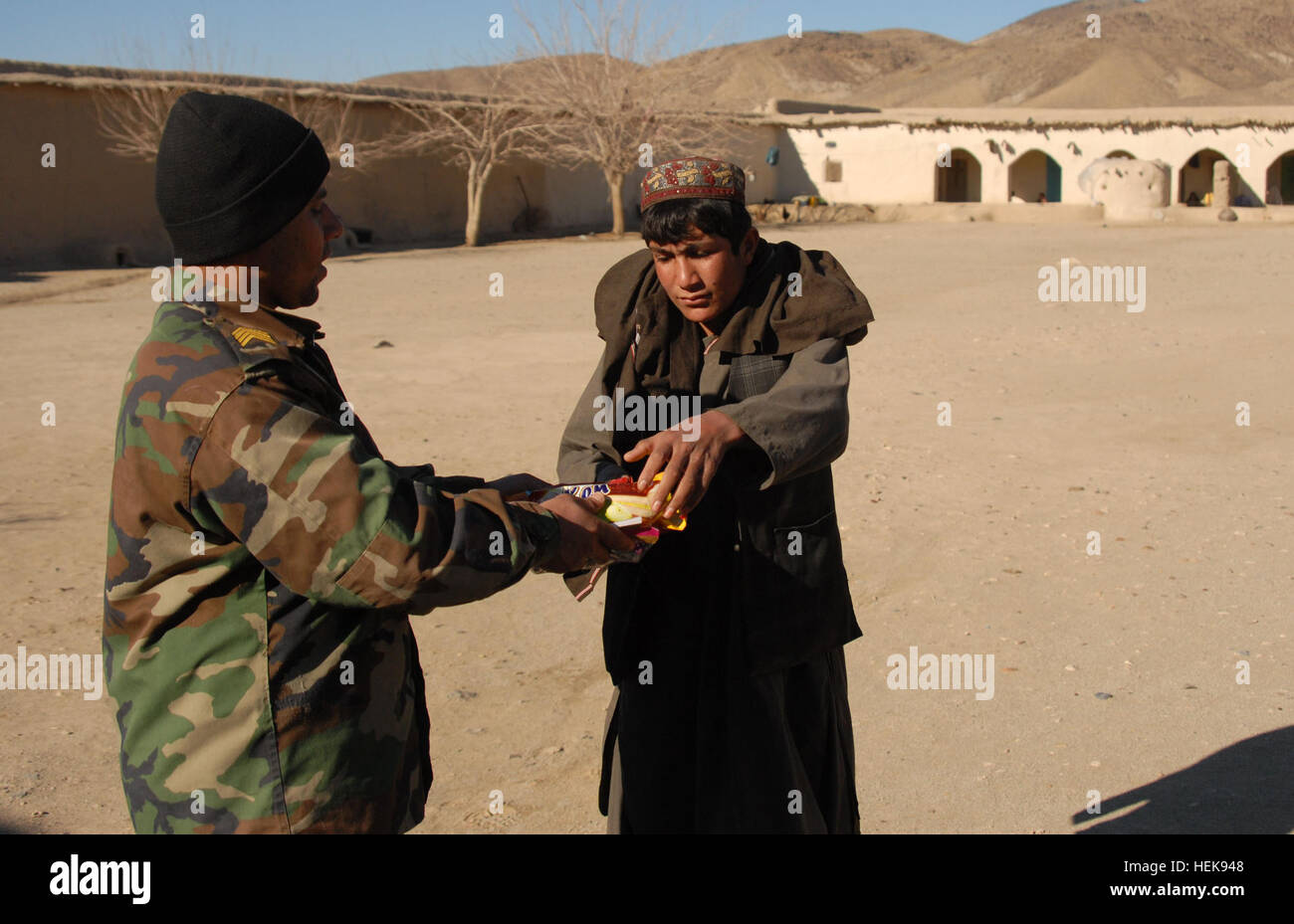 An Afghan Commando from 2nd Company, 3rd Commando Kandak, hands candy he bought from a local shop to a child during - Stock Image