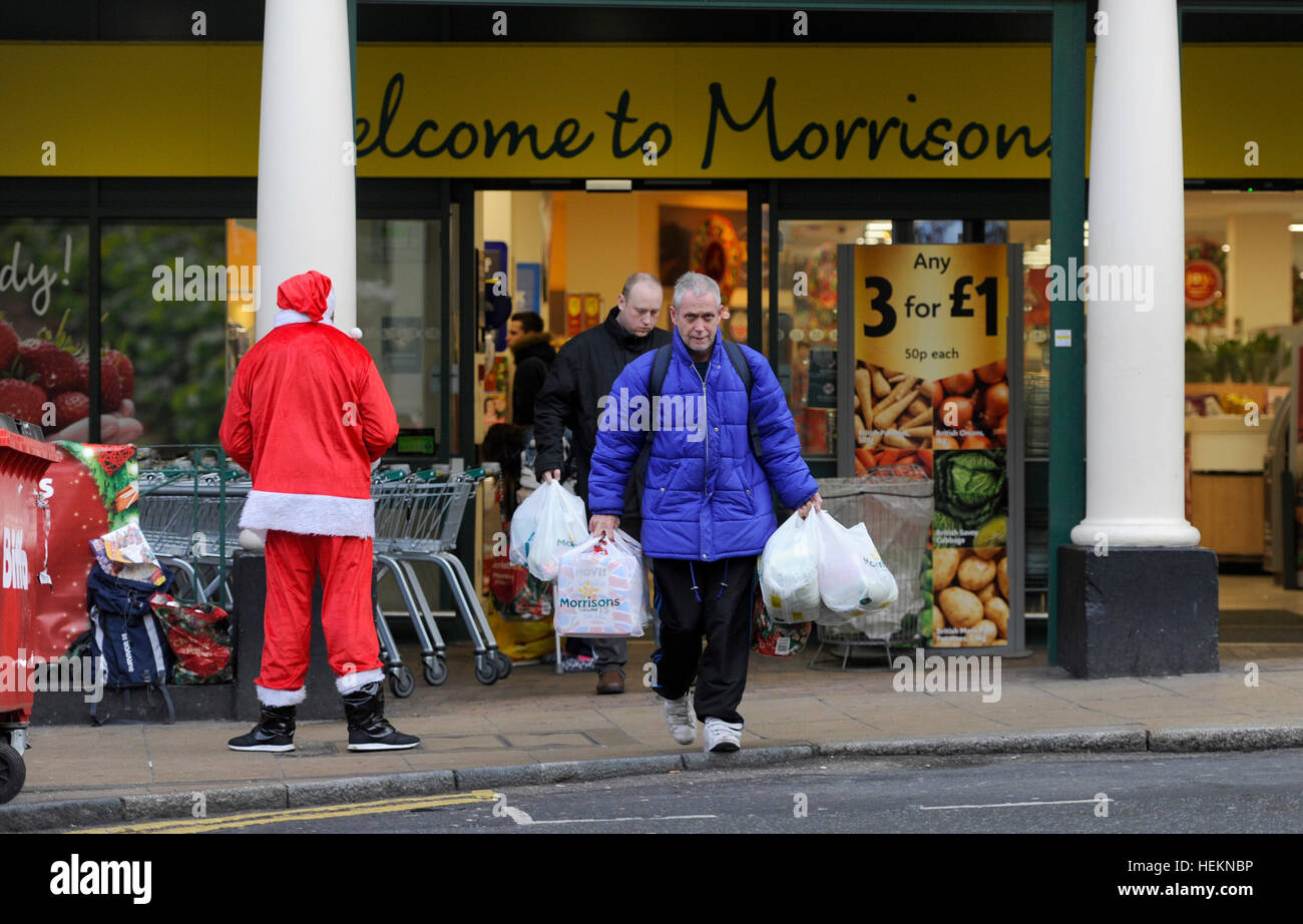 Brighton UK 23rd December 2016 - Shoppers laden with bags pass by a Big Issue seller dressed as Santa as they leave - Stock Image