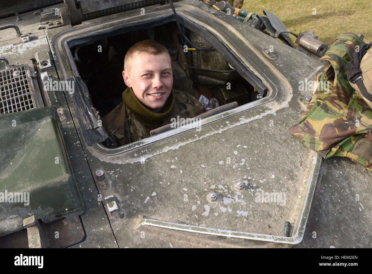 A soldier of the United Kingdom's Mercian Regiment in a Challenger 2 tank drivers seat smiles for the camera - Stock Image