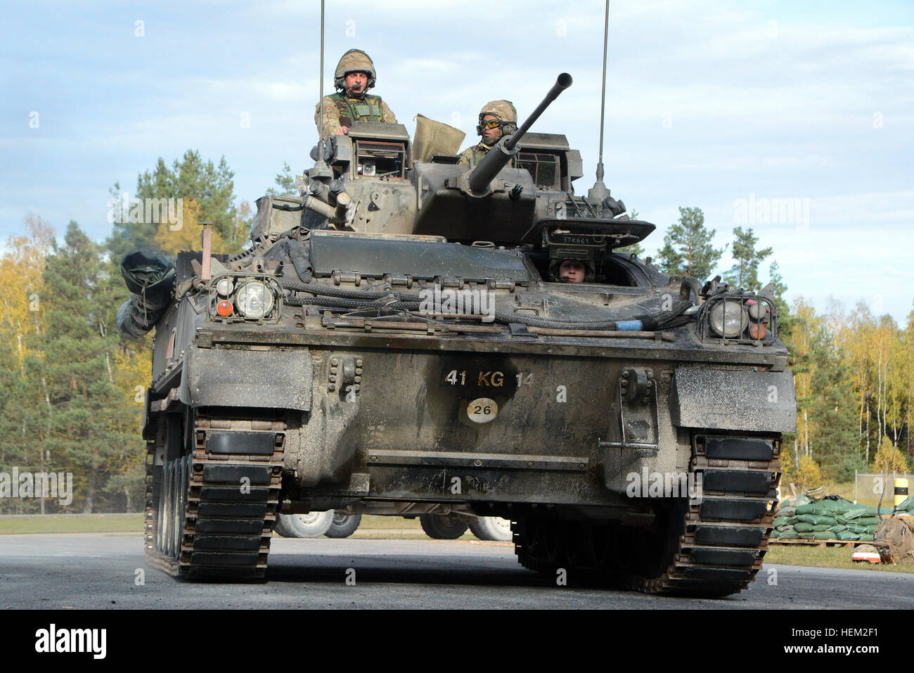 Soldiers of the United Kingdom's Mercian Regiment manuver their Warrior Infantry Fighting Vehicle down a range road - Stock Image
