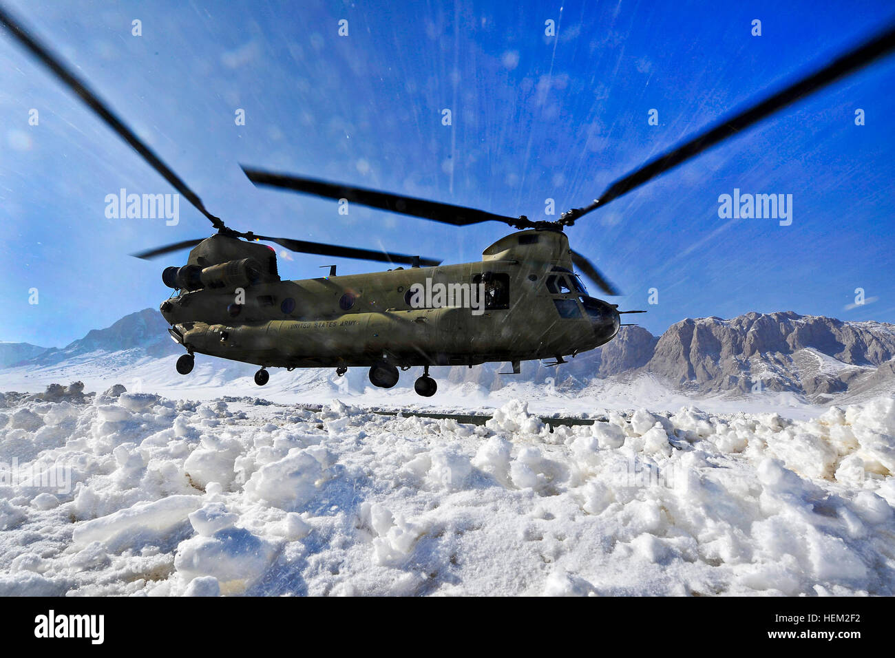 A CH-47 Chinook helicopter raises a white out of blowing snow as it
