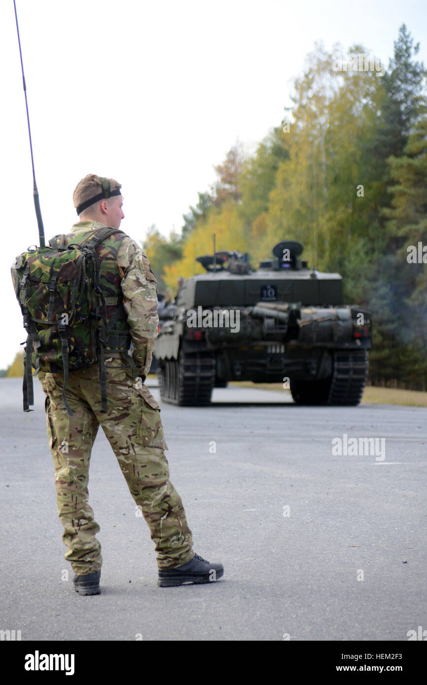 A soldier of the United Kingdom's Mercian Regiment carries radio equipment while a Challenger 2 tank maneuvers - Stock Image