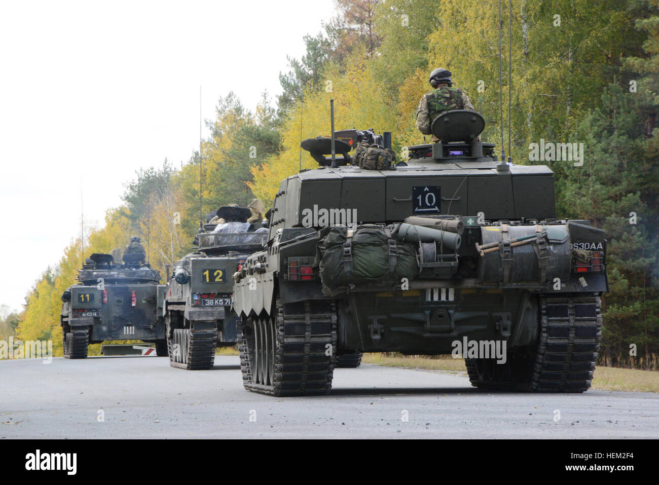 Soldiers of the United Kingdom's Mercian Regiment convoy their tanks down a range road at Grafenwoehr Training Area, - Stock Image