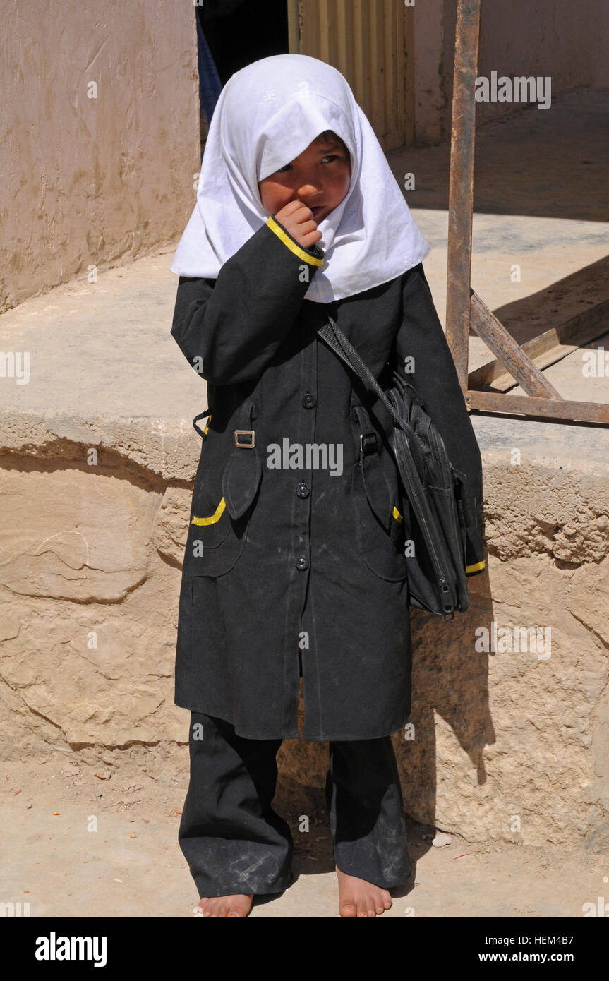 A young Afghan girl stands outside the Aliabad School near Mazar-e-Sharif, Balkh province, Afghanistan, April 3, Stock Photo