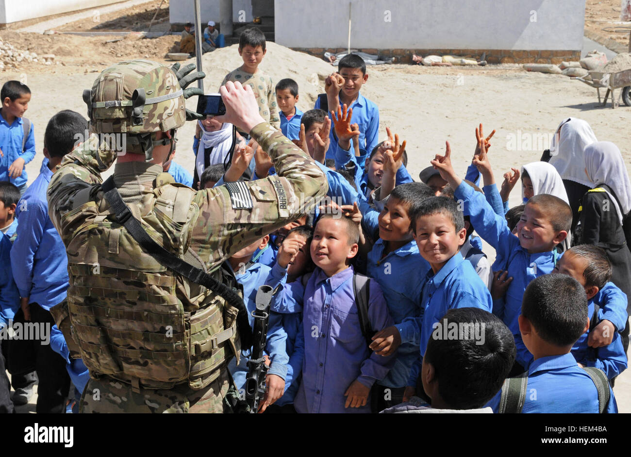 Afghan children wave for the camera of Spc. Aaron Burnside, analyst assigned to Bravo Company, Special Troops Battalion, - Stock Image