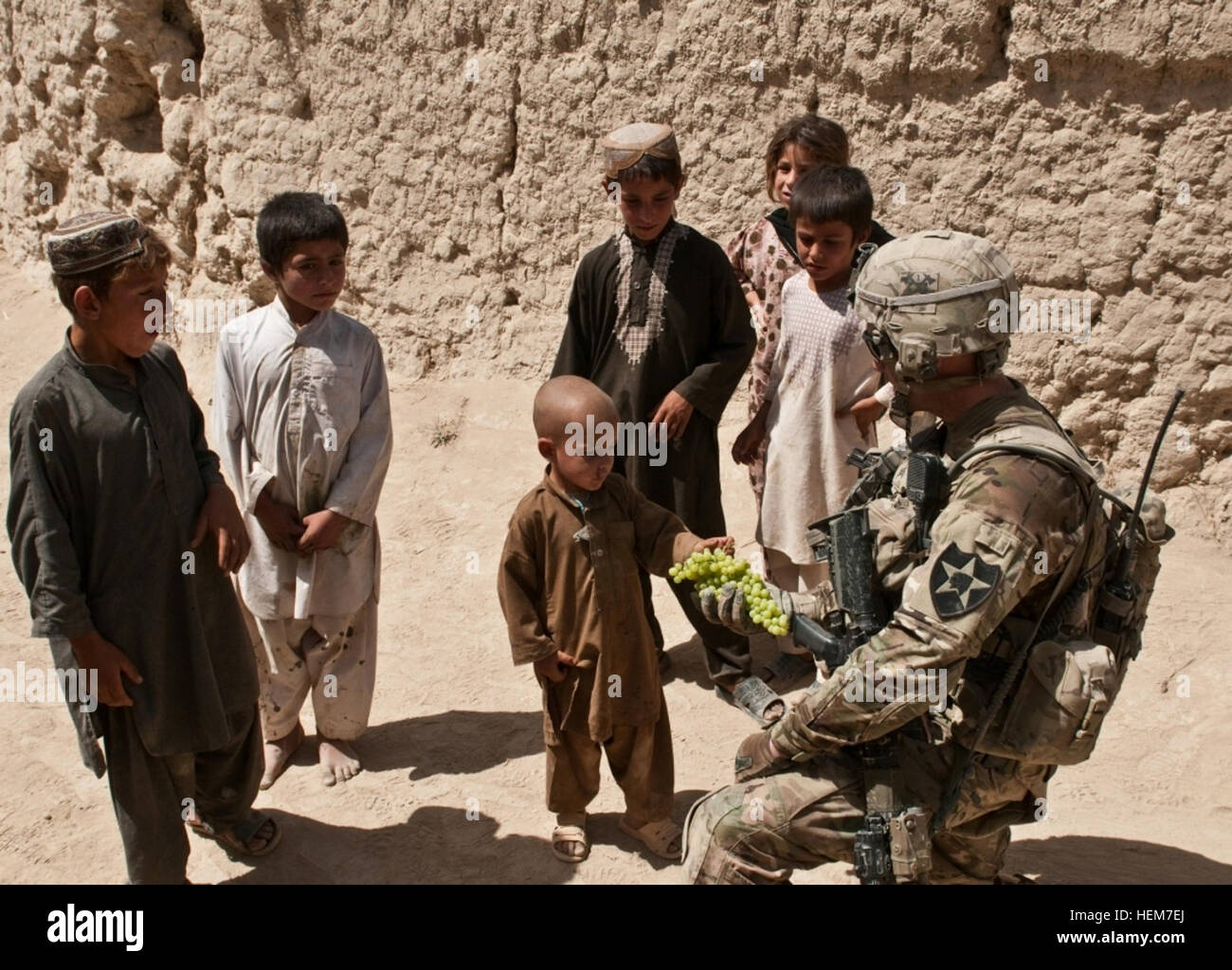 A soldier with 1st Platoon, Bravo Company, 1st Battalion 23rd Infantry Regiment, hands out grapes to curious local - Stock Image