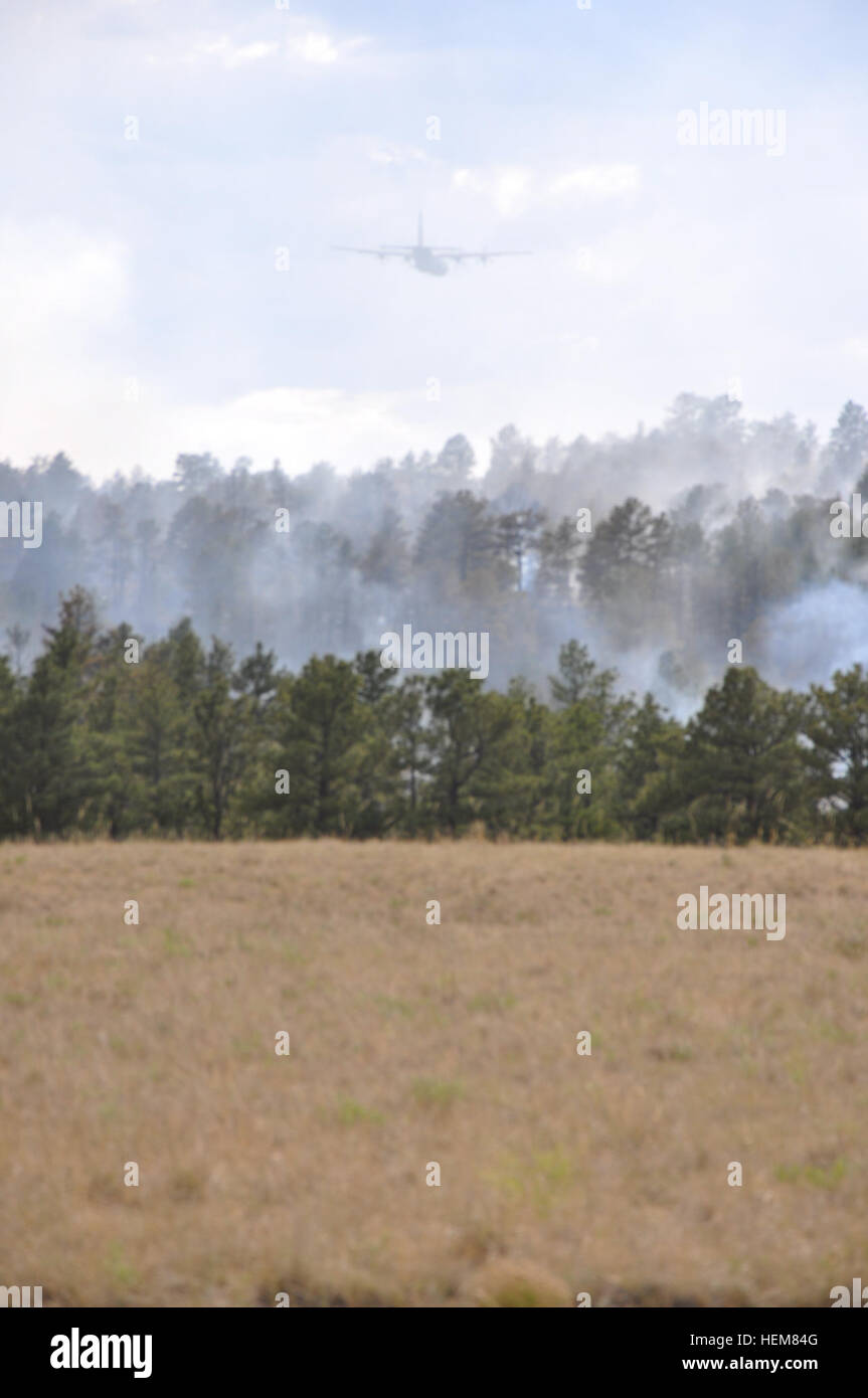A California Air National Guard C-130, carrying the Modular Airborne Fire Fighting System, flies over smoke and - Stock Image