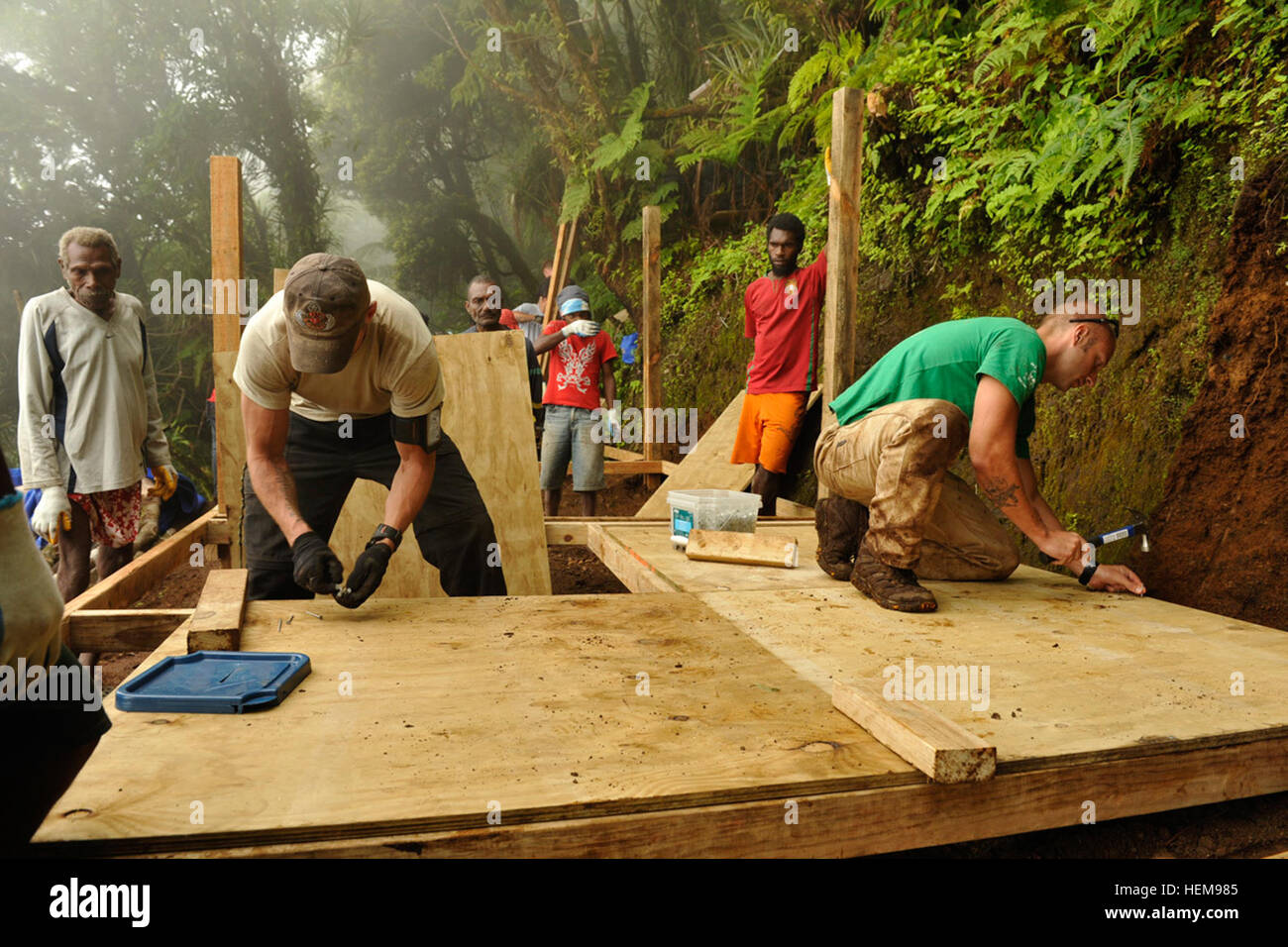 LUGANVILLE, VANUATU -- Service members assigned to the Joint POW/MIA Accounting Command build a platform for a sleeping - Stock Image