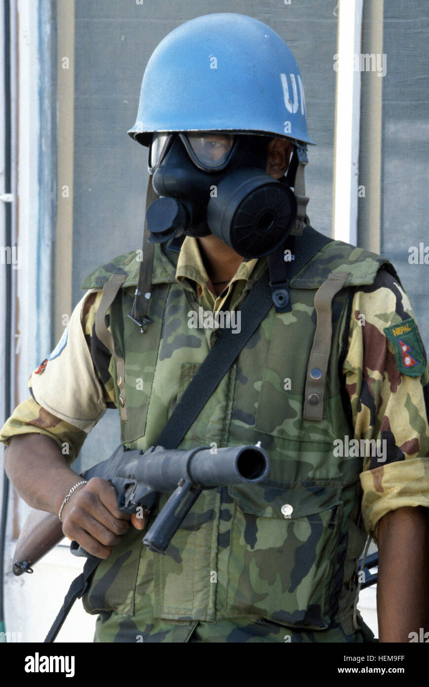 A protective mask and grenade launcher are part of the uniform of this Nepalese soldier.  He is assigned to the - Stock Image