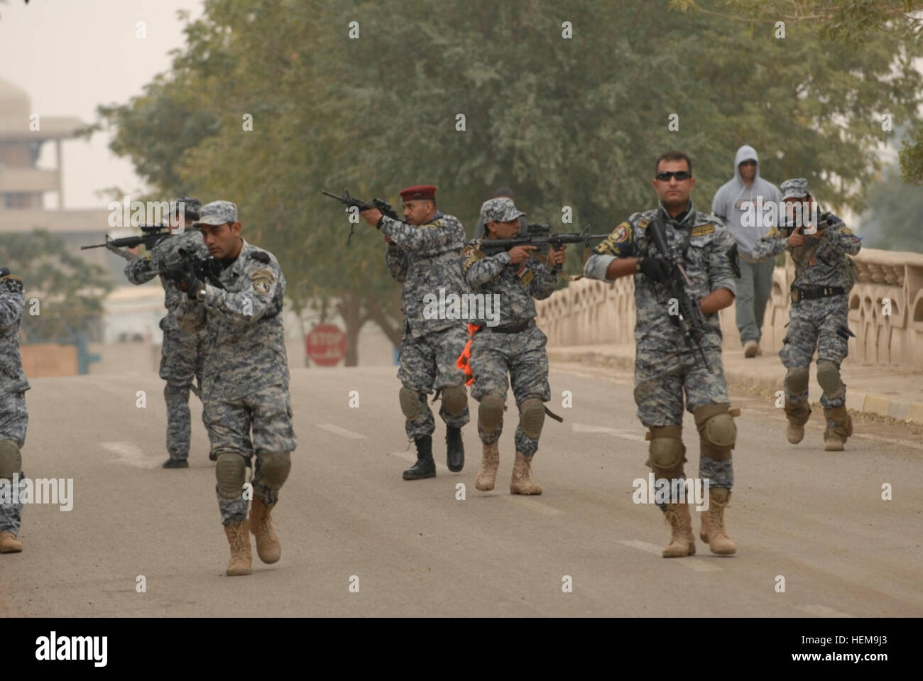 Policemen with the Iraqi Federal Police Explosive Ordnance Disposal Directorates conduct a foot patrol lane during - Stock Image