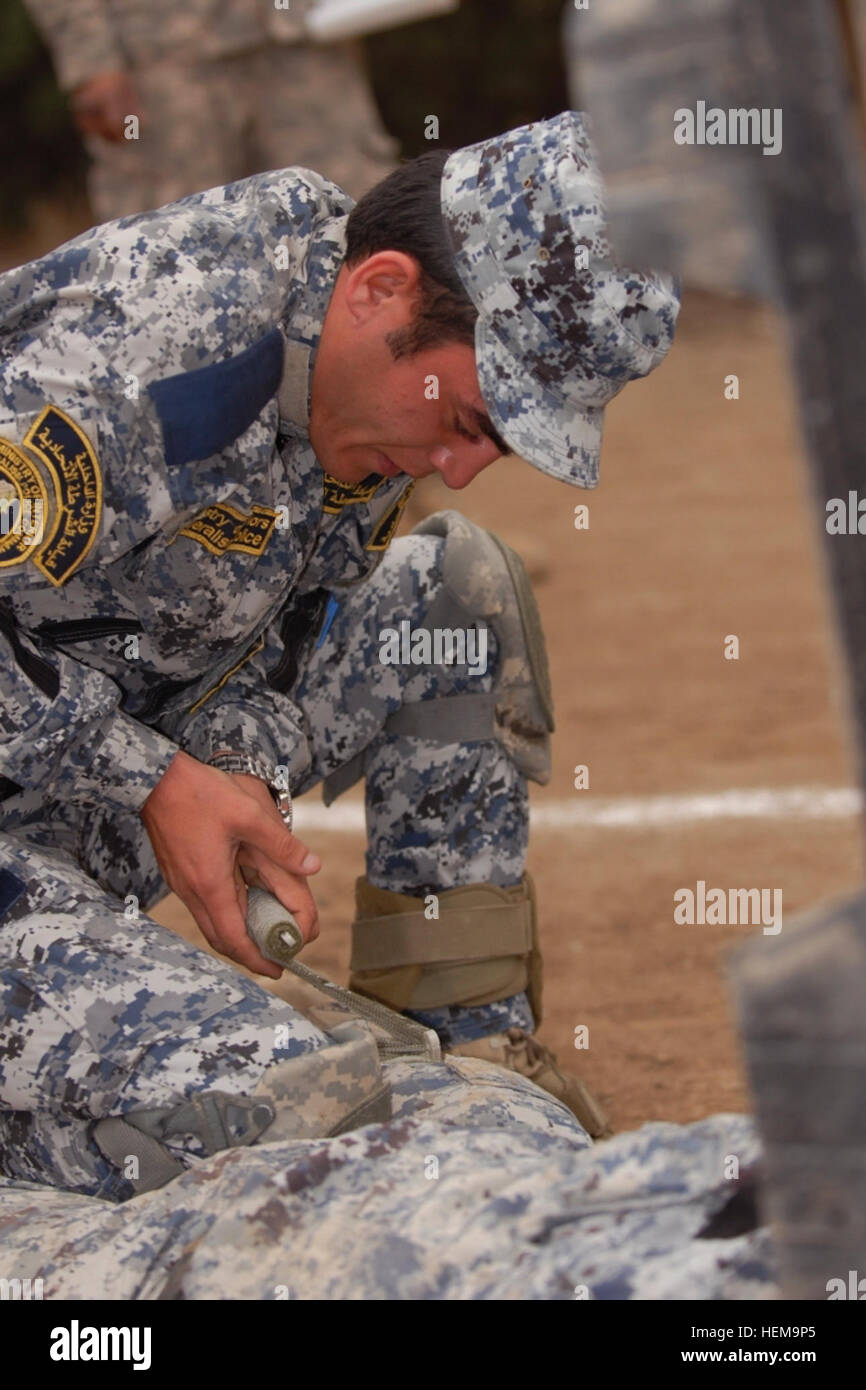 A policeman with the Iraqi Federal Police Explosive Ordnance Disposal Directorates wraps a tourniquet around the - Stock Image