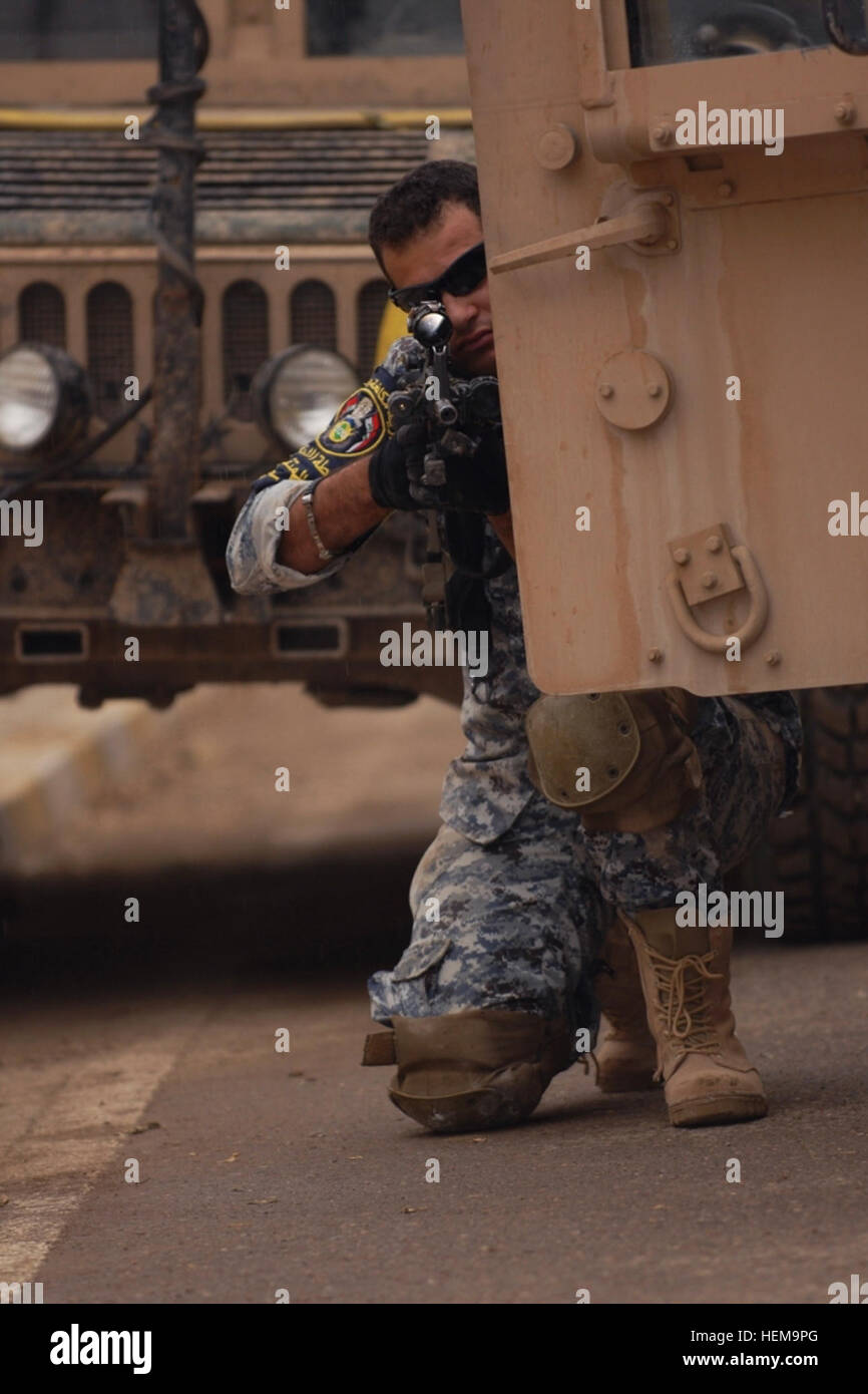 Pvt. Laith Mohammed, a policeman with the Iraqi Federal Police Explosive Ordnance Disposal Directorates, aims his - Stock Image