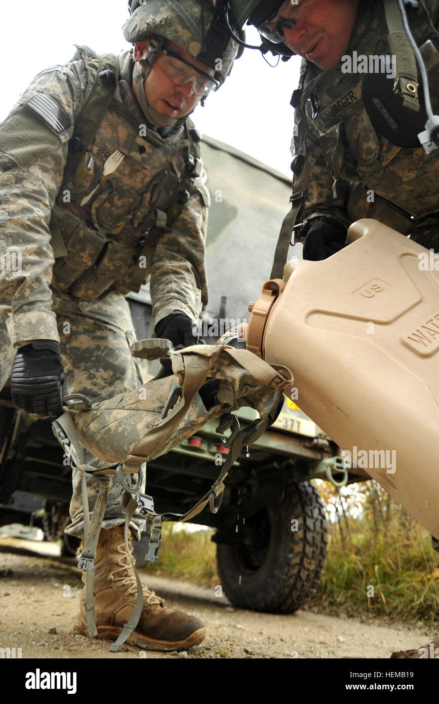 U.S. Army Europe soldiers, assigned to 2nd Cavalry Regiment, fill up their Camelbak with water during Saber Junction - Stock Image