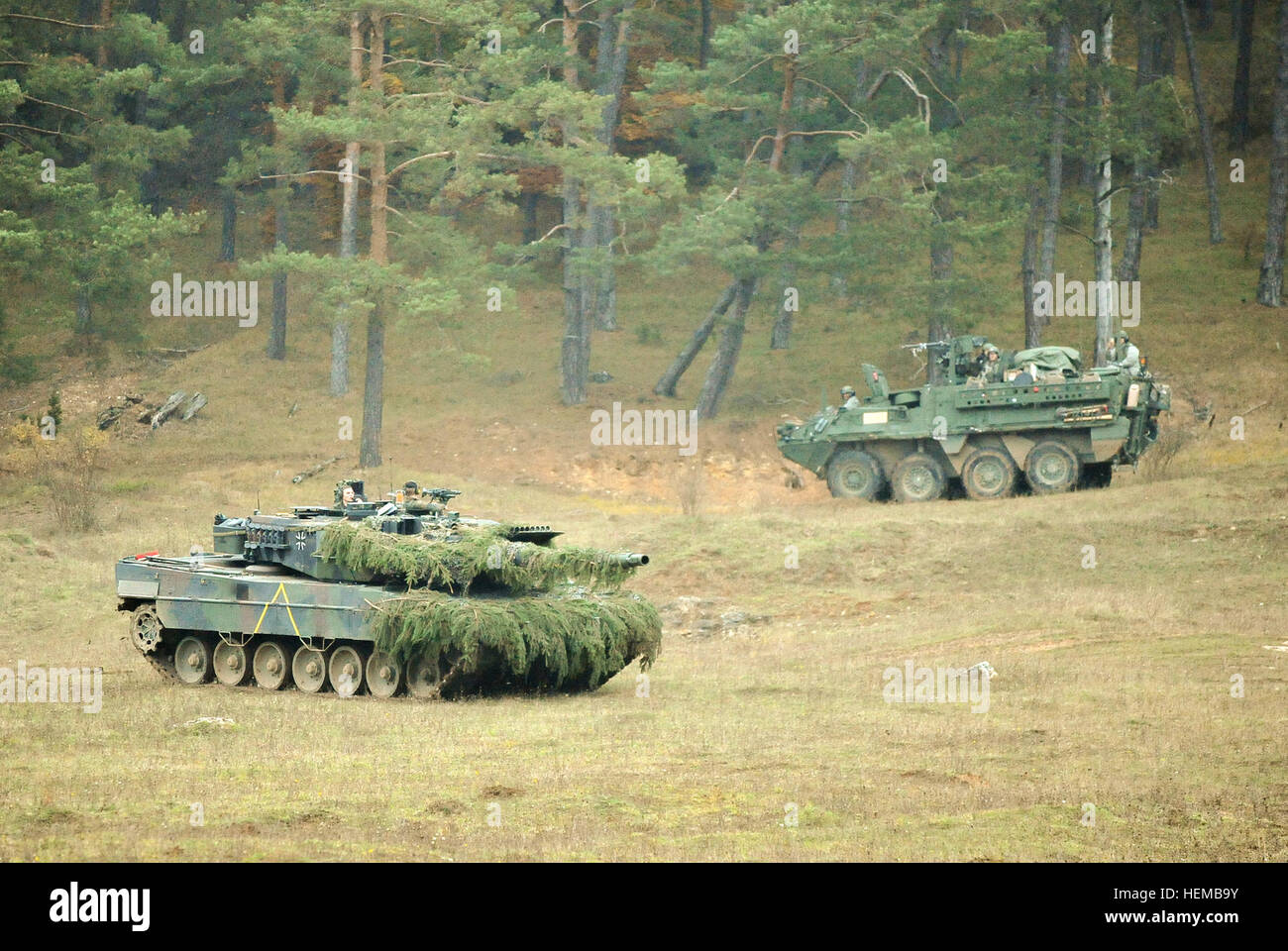 A German Army Leopard II tank, assigned to 104th Panzer Battalion, moves by a U.S. Army Europe Stryker vehicle, - Stock Image