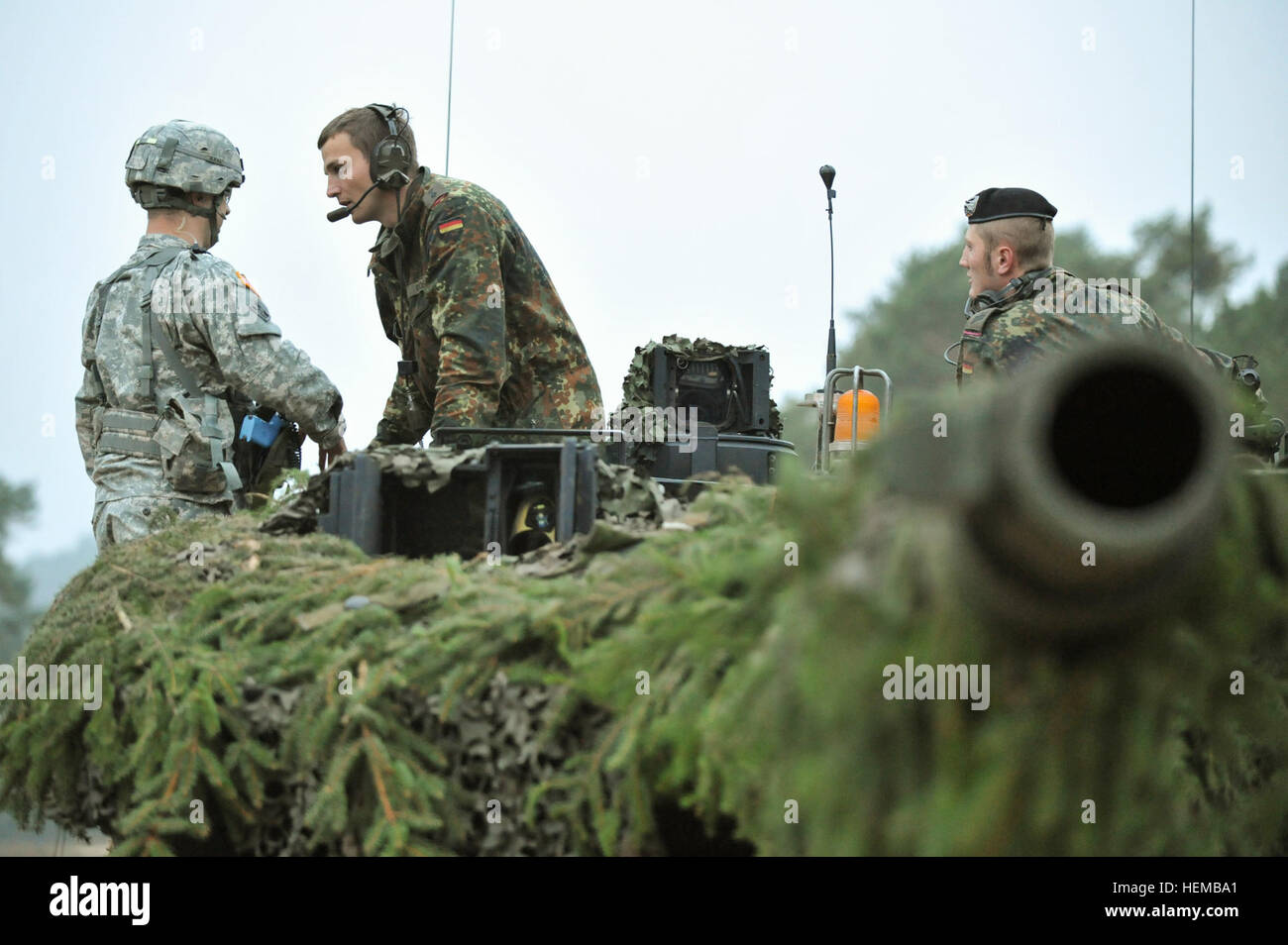 A German Army Leopard II tank commander, assigned to 104th Panzer Battalion, talks to a U.S. Army Europe Observer - Stock Image