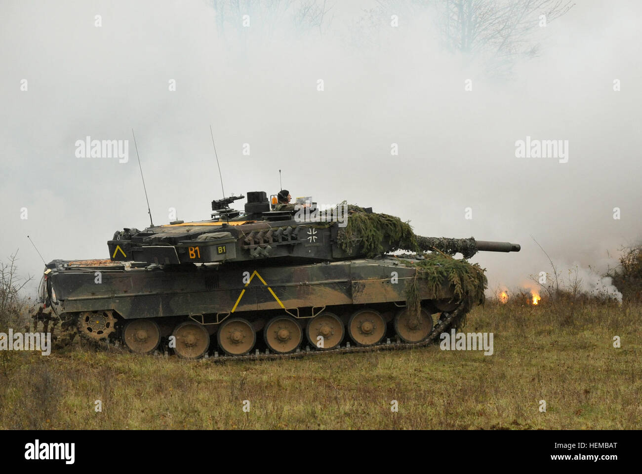 A German Army Leopard II tank, assigned to 104th Panzer Battalion, lays down a cover of white smoke during Saber - Stock Image