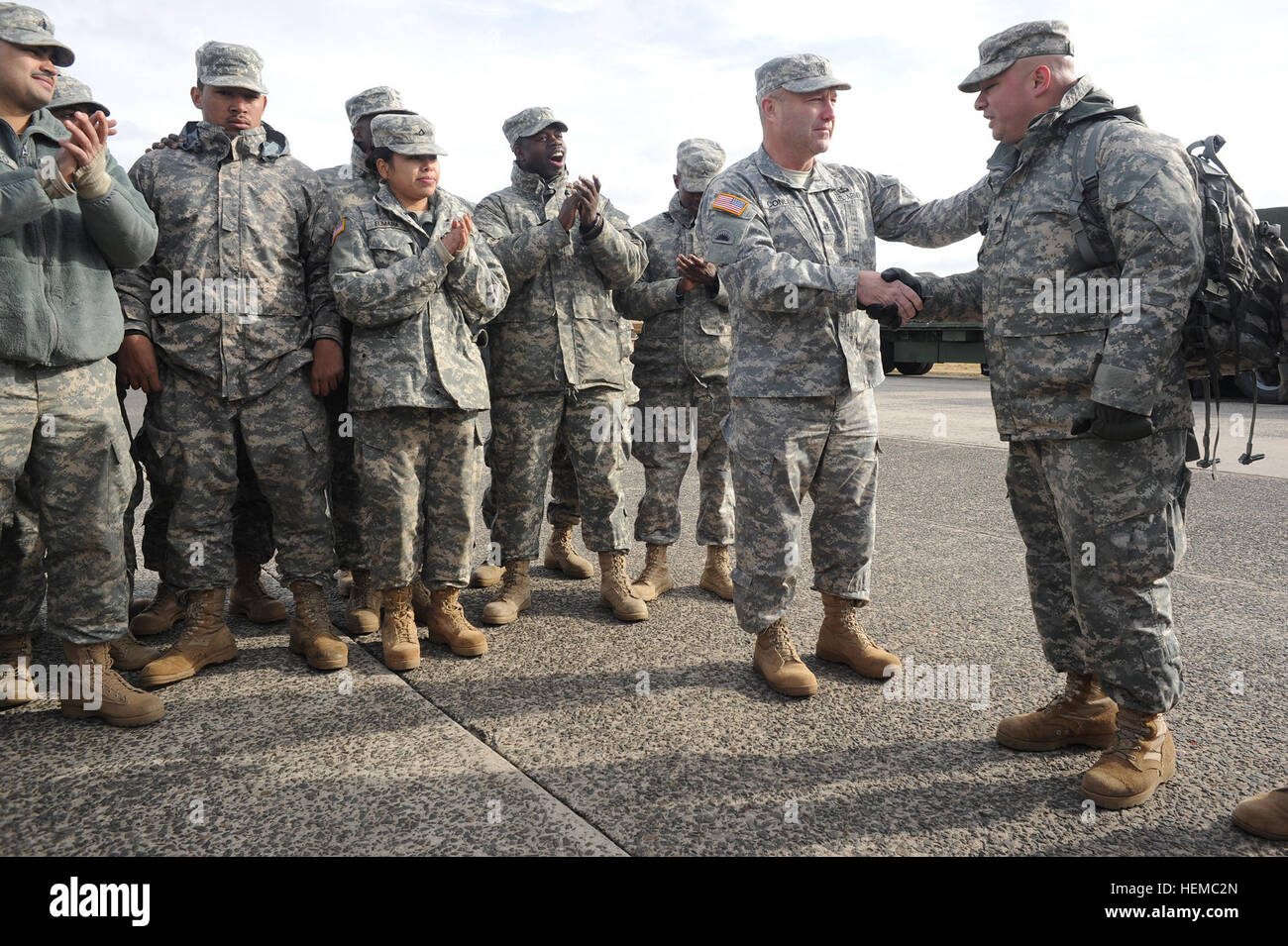 Command Sgt. Maj. Brunk Conley, command sergeant major of the Army National Guard, shakes hands with a soldier from - Stock Image