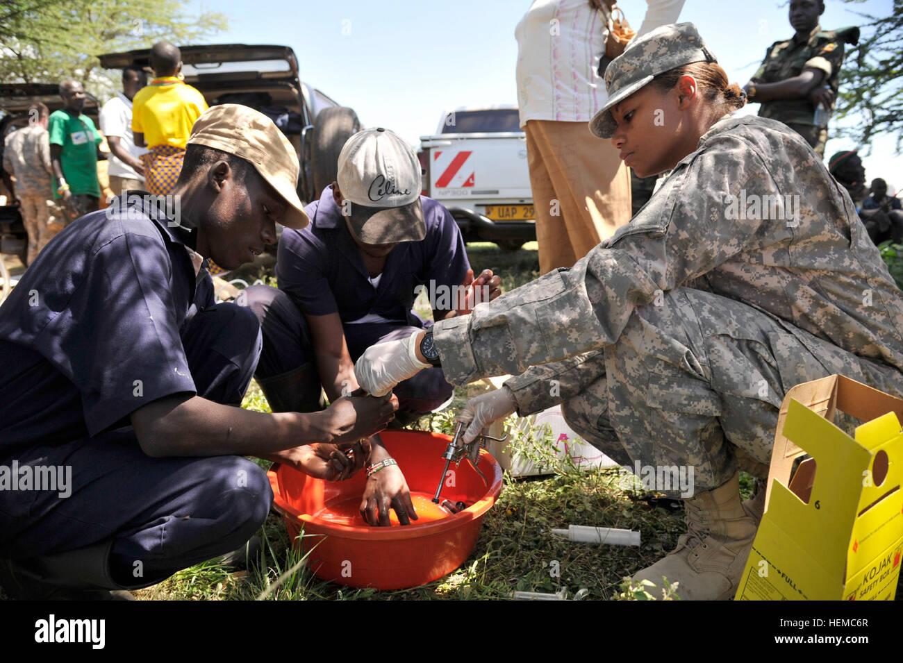 Bogere Paul, left, Waituru Paul, center, and U.S. Army Sgt. Demetria Stewart, right, 448th Civil Affairs Battalion - Stock Image