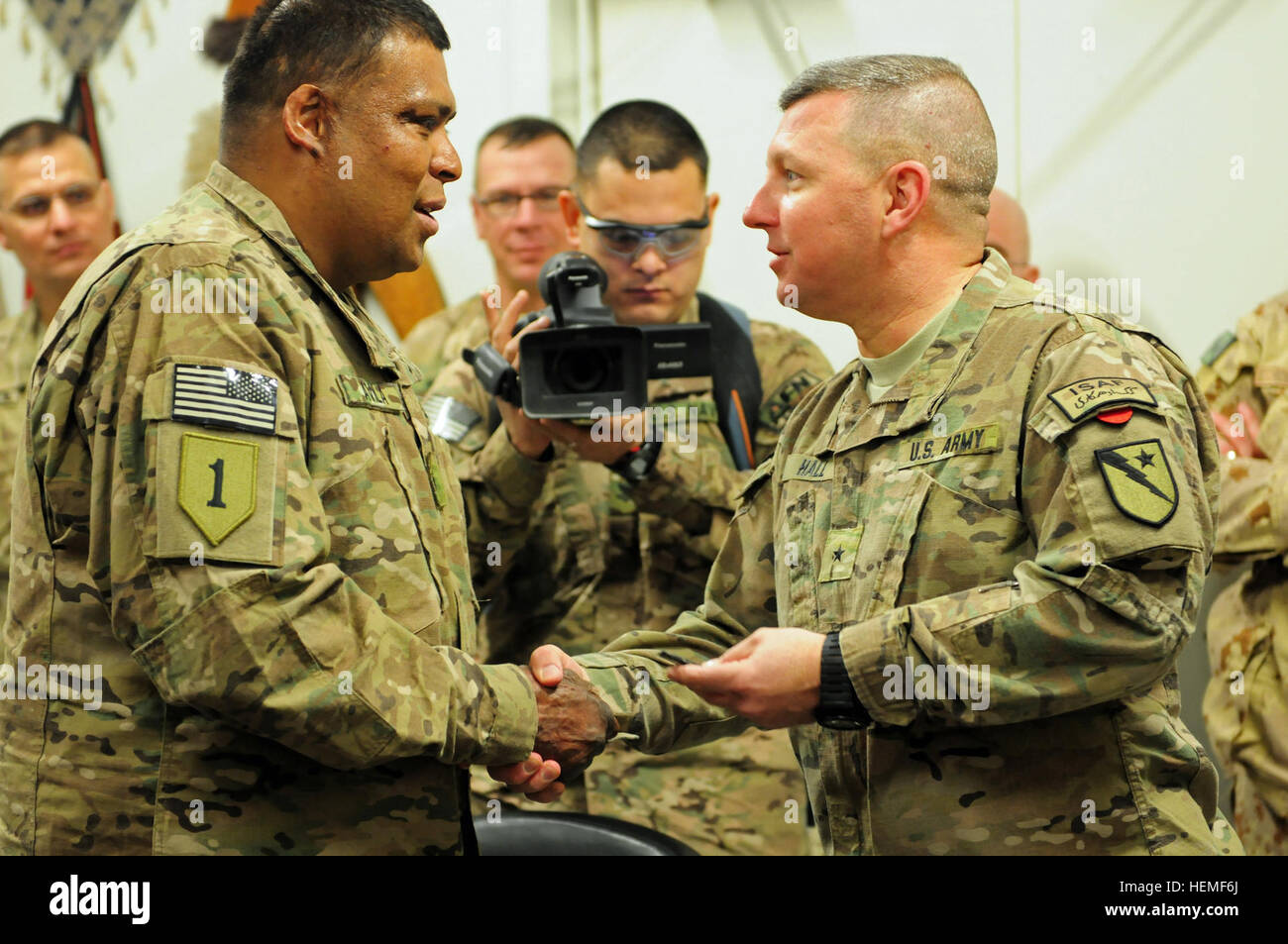 Sgt. Omar Avila, (left) accepts a commander's coin from Brig. Gen. William Hall (right), commander of the 136th - Stock Image