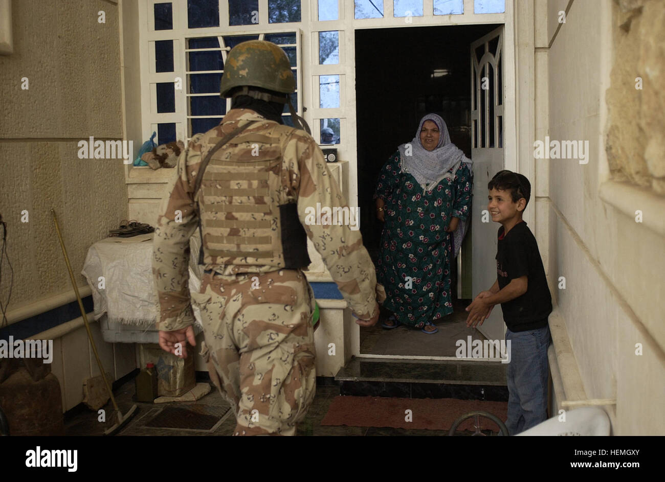 An Iraqi army soldier enters a house to search it while an