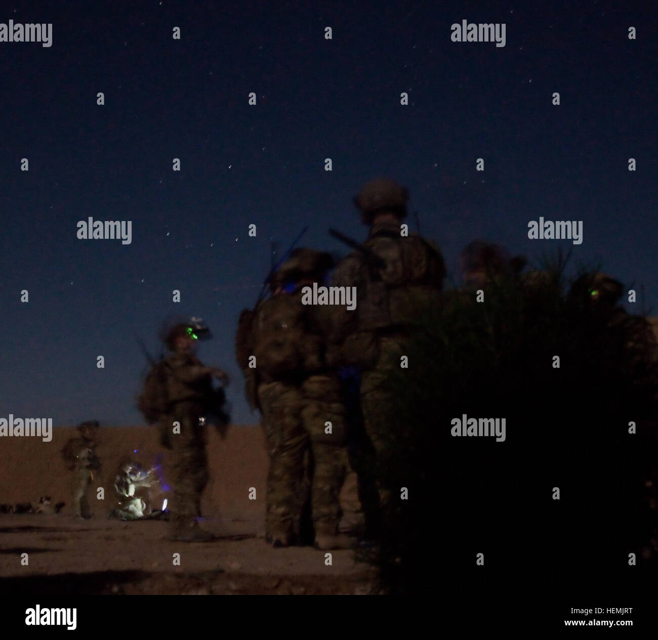Members of an Afghan and coalition security force search the exterior of a Taliban leader's home during an night - Stock Image