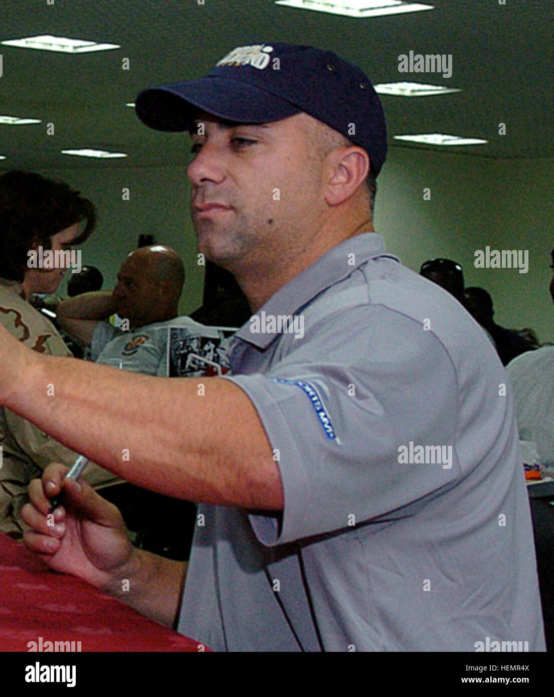 U.S. Navy Lt. Ivory Ervin, from Memphis, Tenn., receives an autographed baseball from Frank Menechino, a 15-year - Stock Image