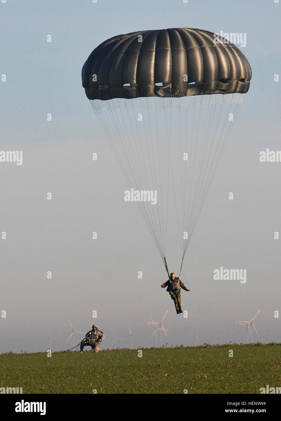 A German paratrooper lands on the Alzey Drop Zone as a paratrooper from the 5th Quartermaster Detachment (Airborne), - Stock Image