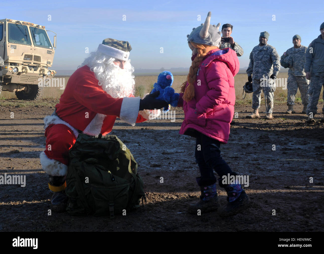 Santa Claus hands out toys to children after performing an airborne jump at the Alzey Drop Zone near Kaiserslautern - Stock Image