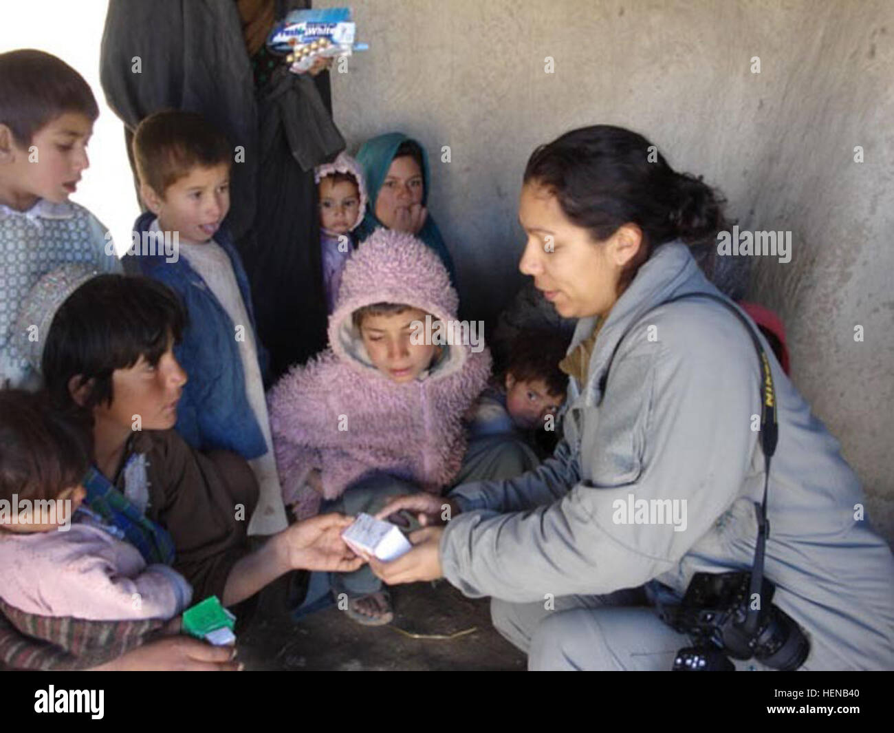 A coalition soldier explains instructions for medications to a young Afghan girl. More than 250 men, women, and - Stock Image