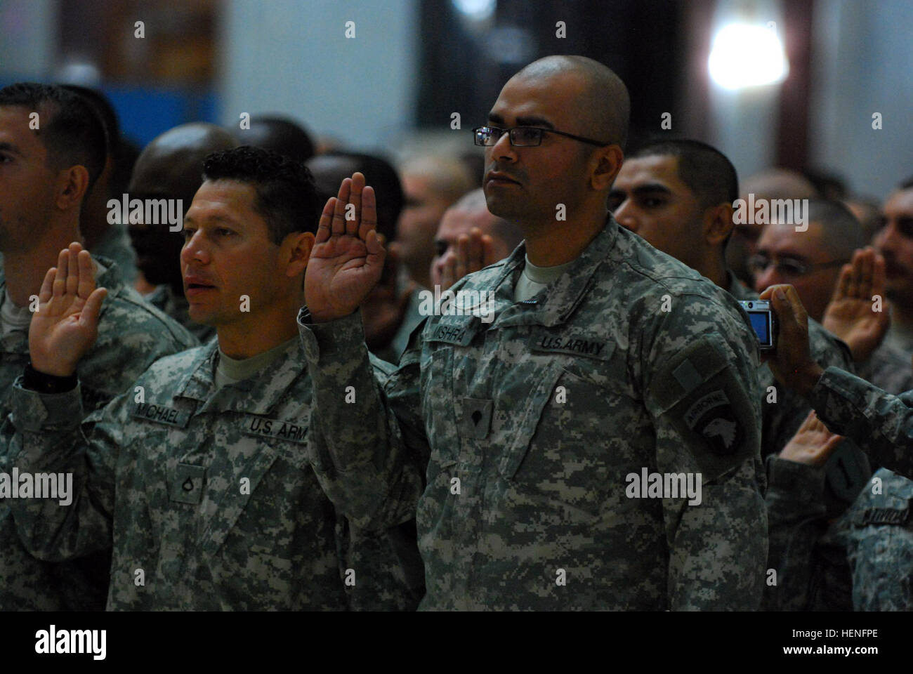 Spc. Vivek Mishra, a native of central India, raises his right hand and recites the Oath of Citizenship during a - Stock Image
