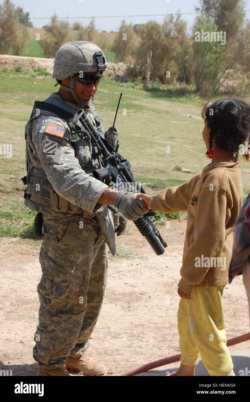 Sgt. Michael Rios, a native of Sebastian, Texas, greets a young girl while on patrol in the Taji Qada, northwest - Stock Image