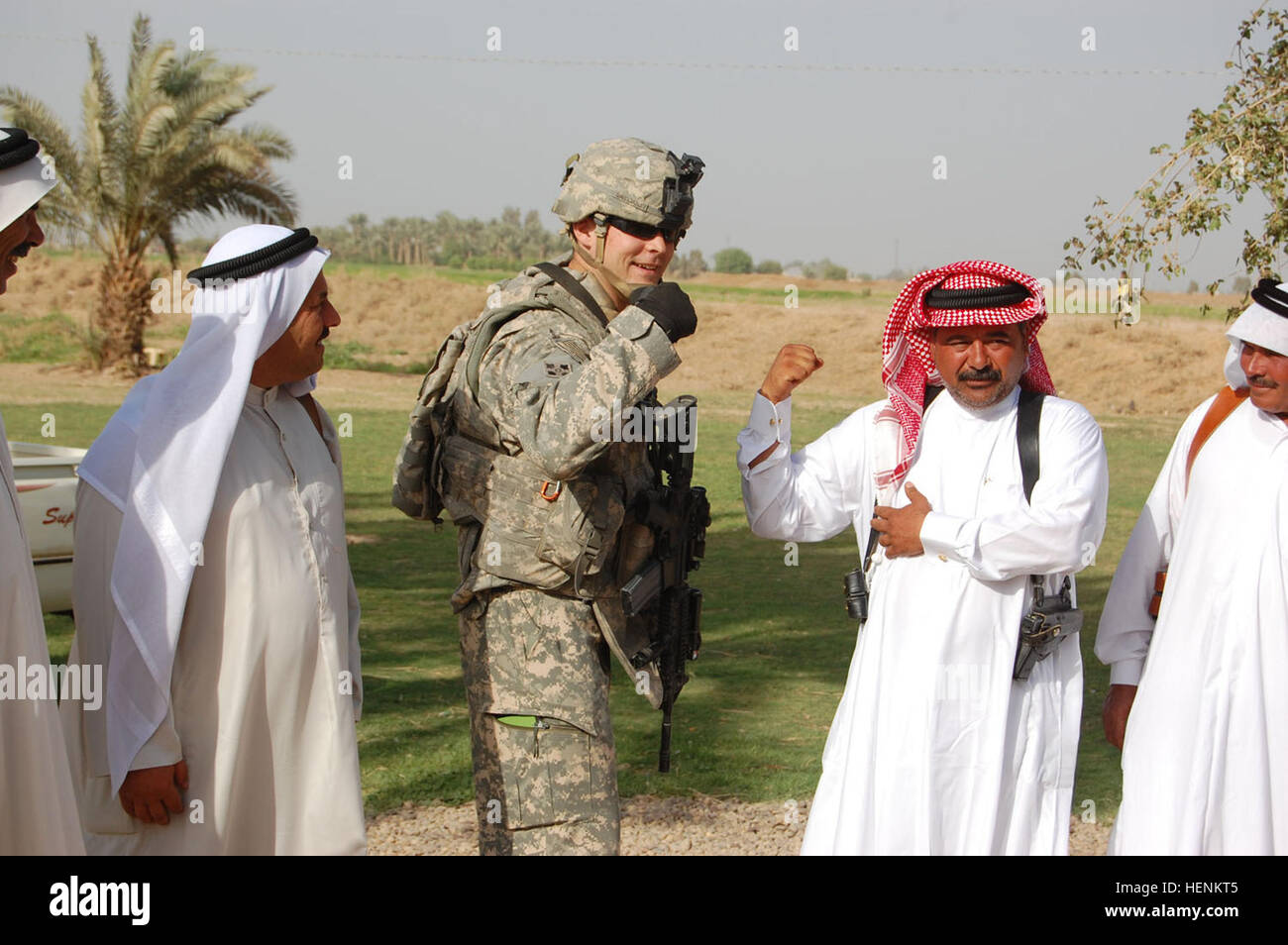 Capt. Brian Sweigart, a native of San Antonio, Texas compares his 'guns' with Iraqis in the Taji Qada, northwest - Stock Image