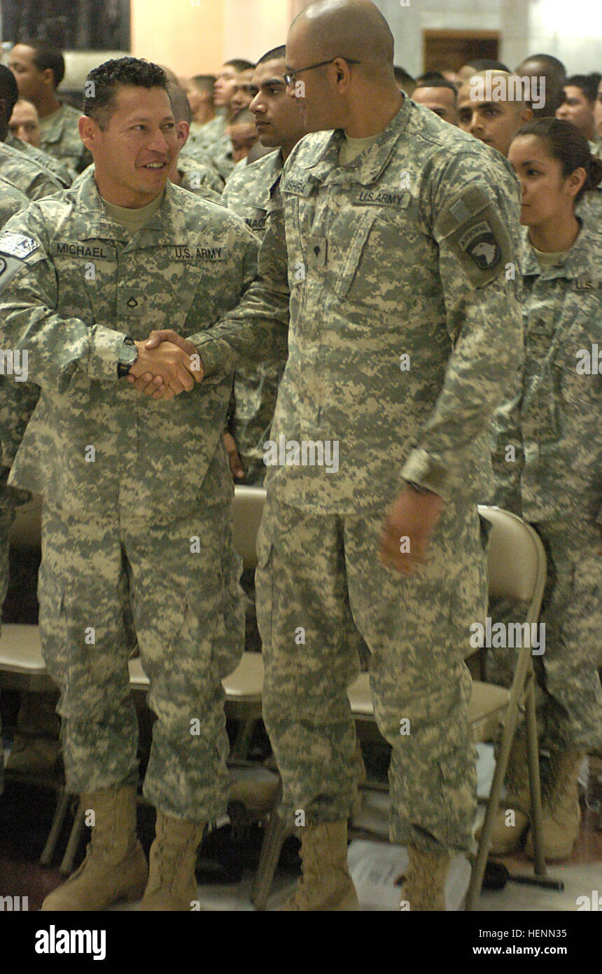 Spc. Vivek Mishra (right) with the 101st Airborne Division, shakes hands with Pfc. Henry Michael, 72nd Military - Stock Image
