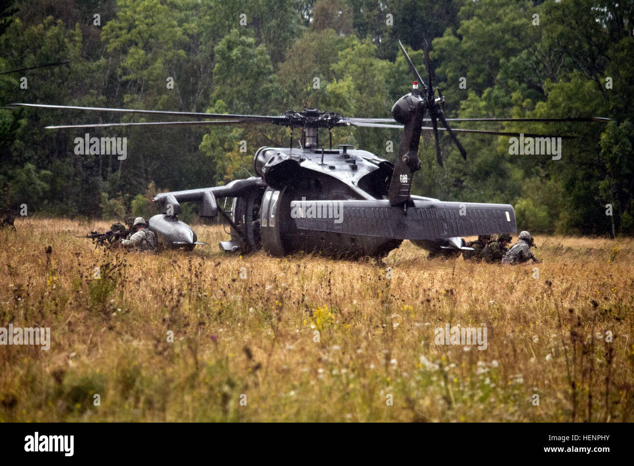 American paratroopers and Estonian soldiers exit a UH-60 Black Hawk Helicopter from the 12th Combat Aviation Brigade during an air assault training mission held Aug 22-24 in Paldiski, Estonia. The three-day exercise featured troops from Company B, 2nd Battalion, 503rd Infantry Regiment, 173rd Airborne Brigade and the Estonian Defense Forces' Single Scouts Infantry Battalion executing day and night assaults. The training is part of Operation Atlantic Resolve, an exercise dedicated to demonstrating commitment to NATO obligations and maintaining interoperability with allied forces. Heroes on helo Stock Photo