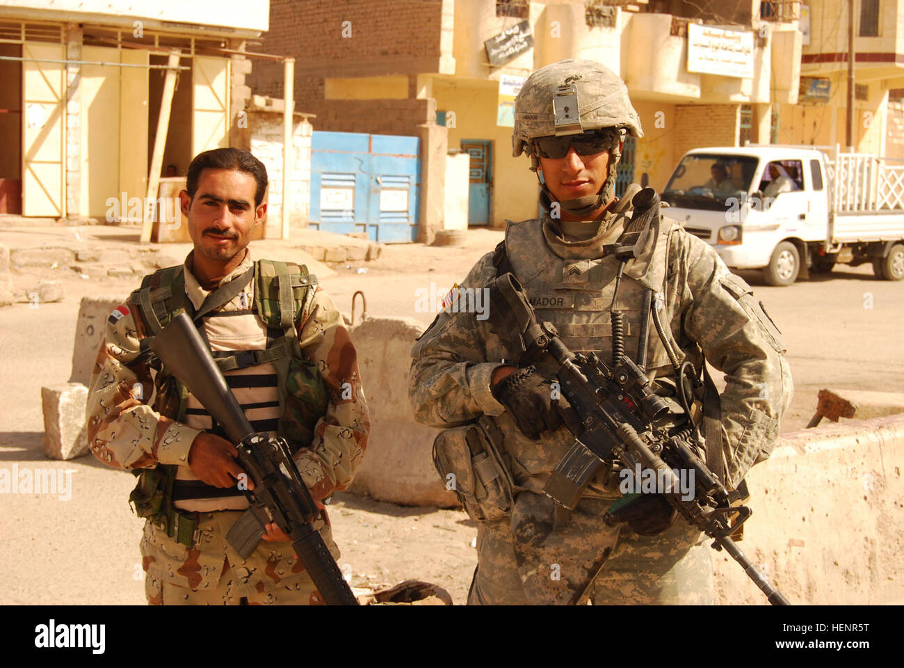 Sgt. Eugenio Amador, a native of Miami, stands with an Iraqi army soldier at a joint checkpoint at Nassir Wa Salam, - Stock Image