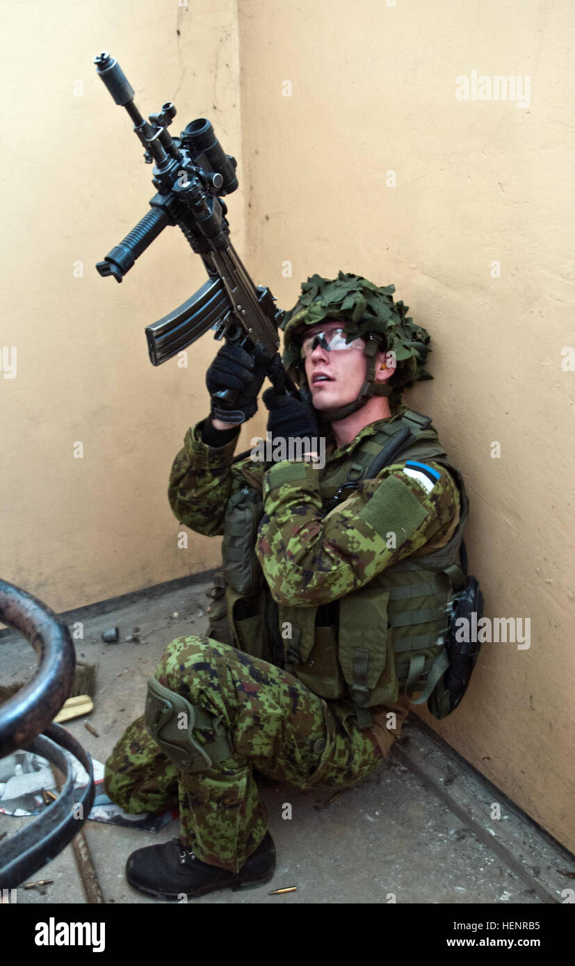 An Estonian Defense Forces soldier from Company C, Single Scouts Infantry Battalion looks up a stairwell in search Stock Photo