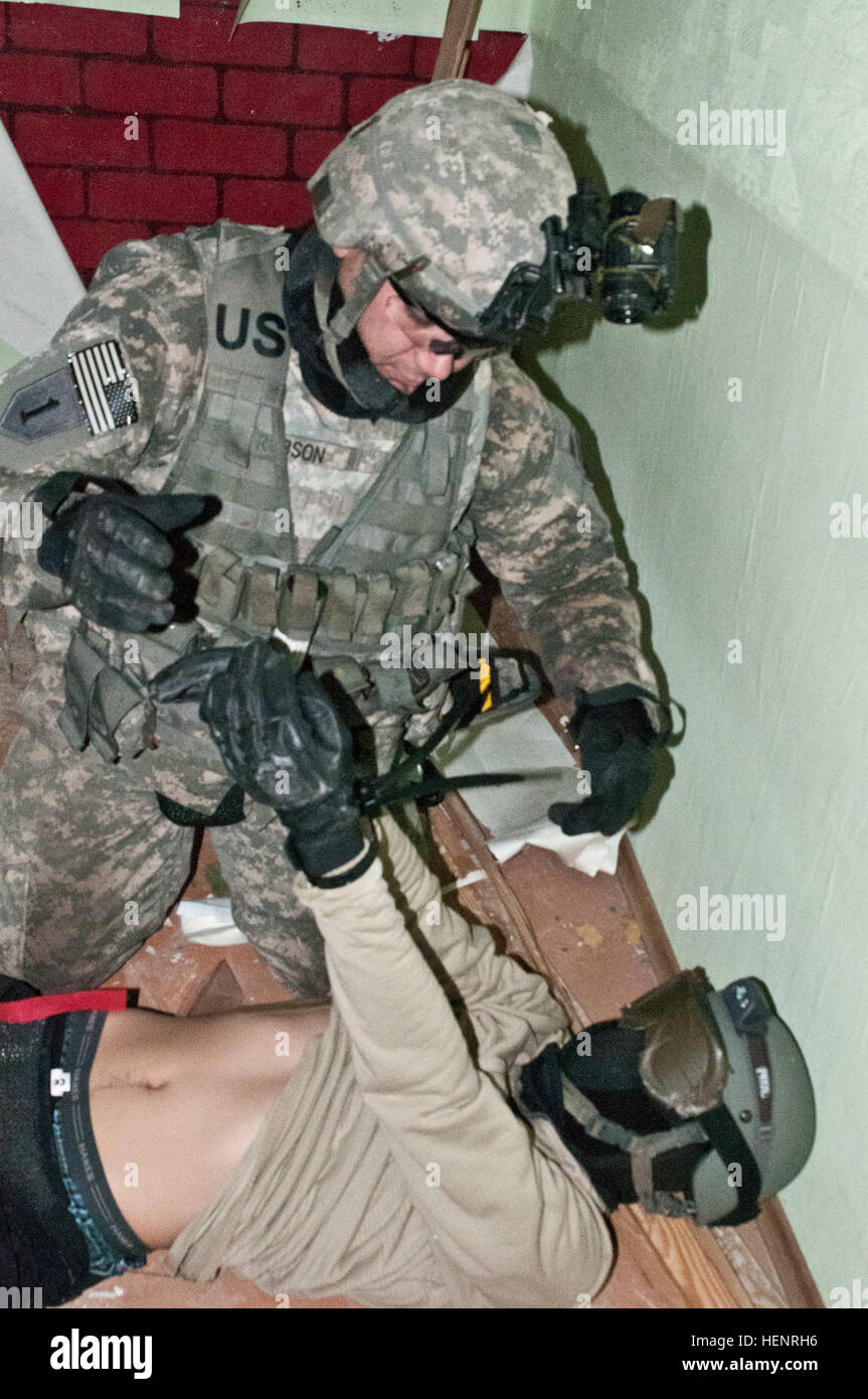 Spc. William S. Robson V [the fifth] (left), an Athens, Texas native serving as an infantryman in Company B, 2nd Battalion, 503rd Infantry Regiment, 173rd Airborne Brigade restrains a Soldier role-playing as a wounded insurgent during a night raid training mission held Sept. 6-7 at an abandoned prison in Rummu, Estonia. The raid was part of Steadfast Javelin II, a NATO exercise involving more than 2,000 troops from nine nations conducting various training missions across Estonia, Germany, Latvia, Lithuania and Poland. The exercise focuses on increasing interoperability and synchronizing comple Stock Photo