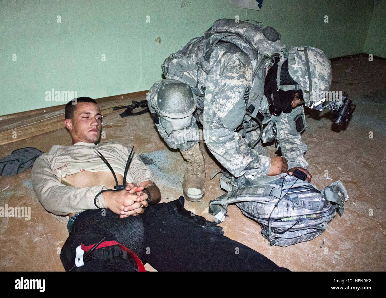 Army Pfc. Charles E. Jacobo, an Anaheim, California, native serving as a health care specialist in Company B, 2nd Battalion, 503rd Infantry Regiment, 173rd Airborne Brigade applies first aid to a Soldier role-playing as a wounded insurgent during a night raid training mission held Sept. 6 at an abandoned Soviet era prison in Rummu, Estonia. The raid was part of Steadfast Javelin II, a NATO exercise involving more than 2,000 troops from nine nations conducting various training missions across Estonia, Germany, Latvia, Lithuania and Poland. The exercise focuses on increasing interoperability and Stock Photo