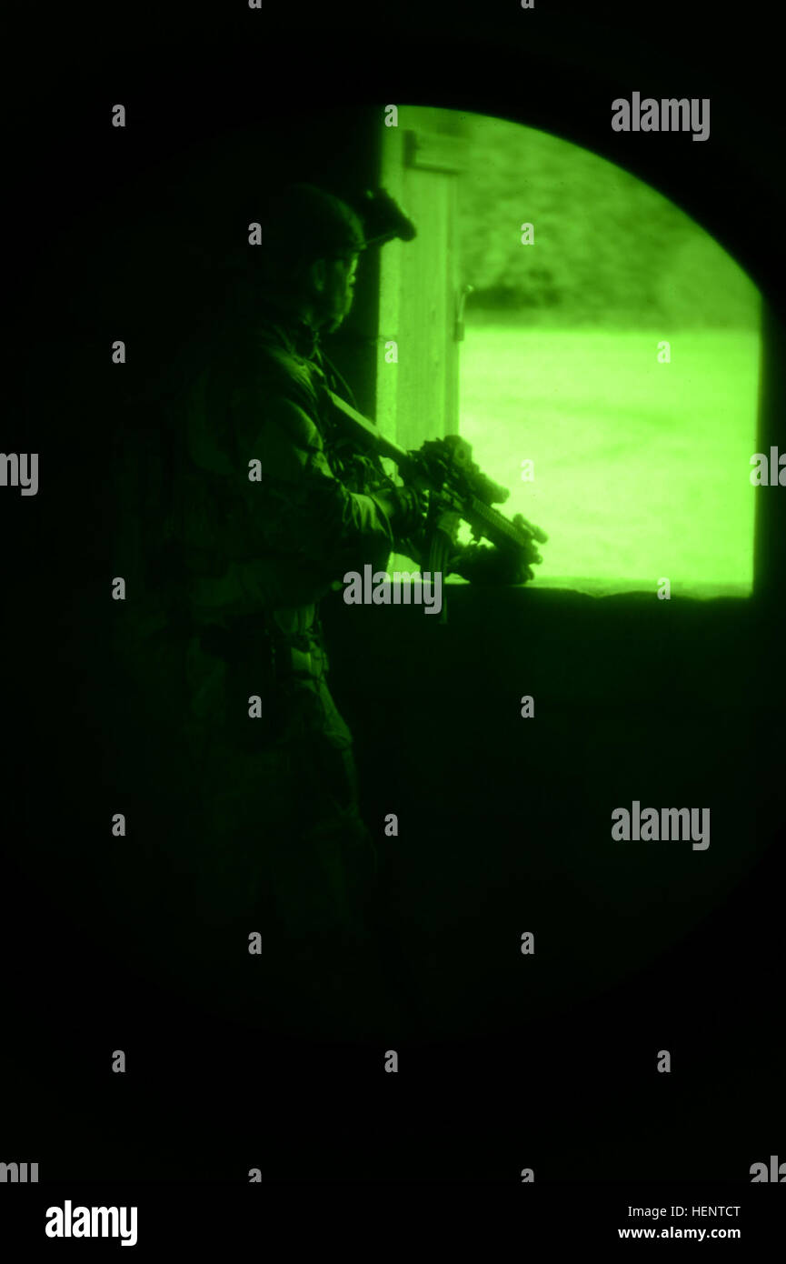 A soldier, from 1st Battalion, 10th Special Forces Group, watches from a window during the special operations training, - Stock Image