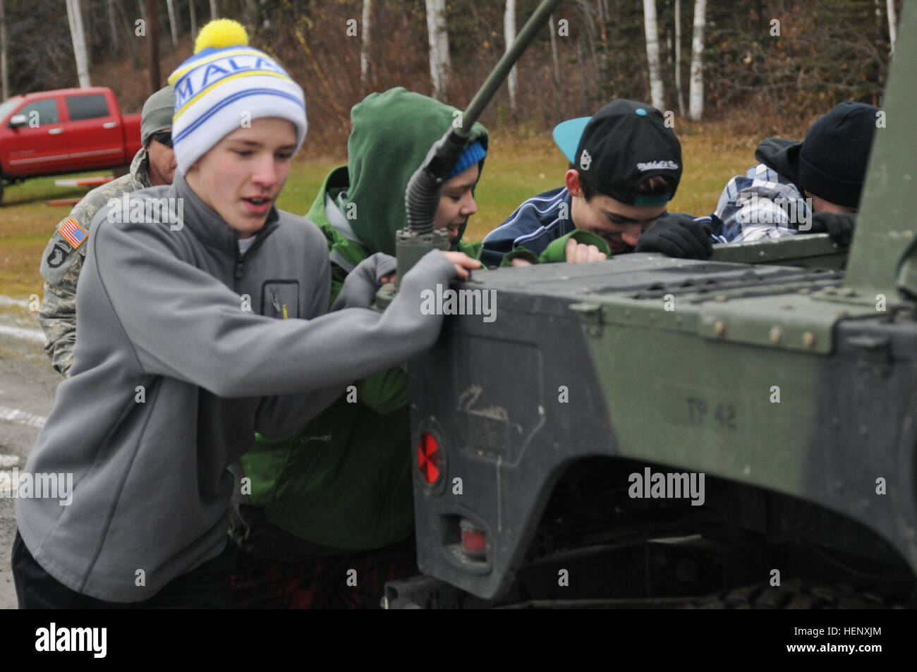 Hockey team players from Eagle River High School work together as they push a Humvee during a leadership development - Stock Image