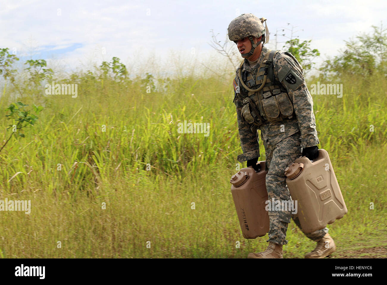 Army Sgt. Gregory J. Maldonado carries two water canisters as part of the third station of the obstacle course for - Stock Image
