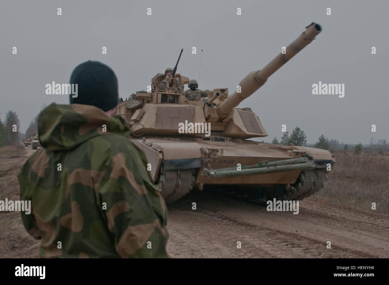 Grenadier Jonricard Schau, a Norwegian sapper, looks on as a U.S. Army M1A2 Abrams Tank moves past the defensive Stock Photo