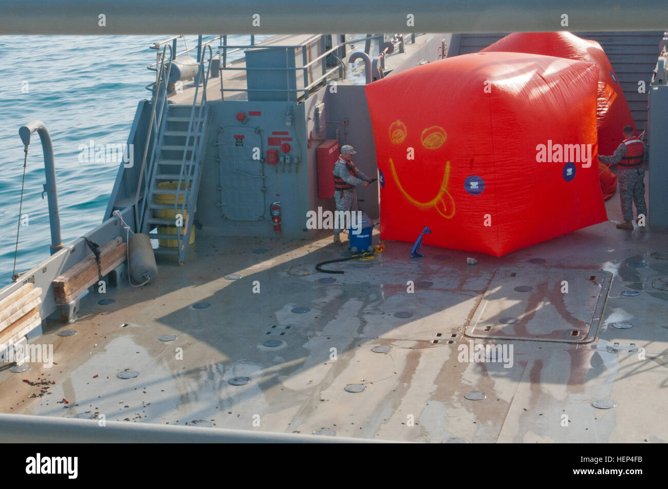 "Two of the crewmembers aboard the U.S. Army Vessel Corinth, inflate and secure the waterborne targets called ""Killer - Stock Image"