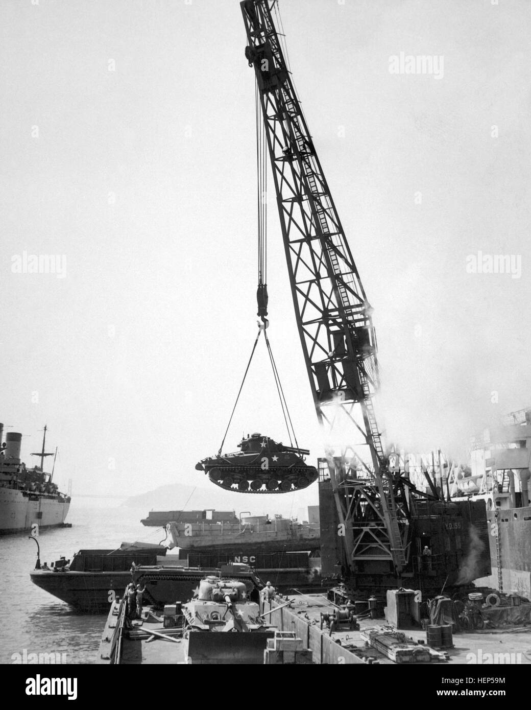 Marine Corps tanks - ready for the front lines - are swung aboard a barge at the Naval Supply Center by crane, for - Stock Image