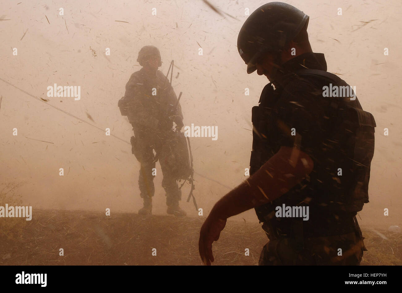 The rotor wash from a UH-60 Blackhawk helicopter temporarily blinds an Iraqi SWAT policemen and his U.S. counterpart. - Stock Image